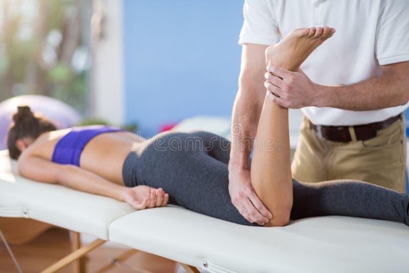 Manlig fysioterapeut som ger knämassage till den kvinnliga patienten royaltyfri foto