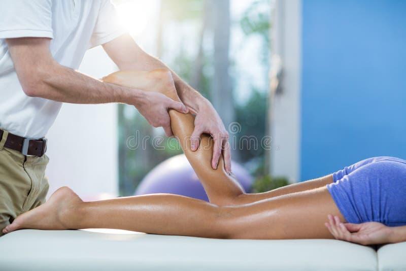 Manlig fysioterapeut som ger knämassage till den kvinnliga patienten arkivbild