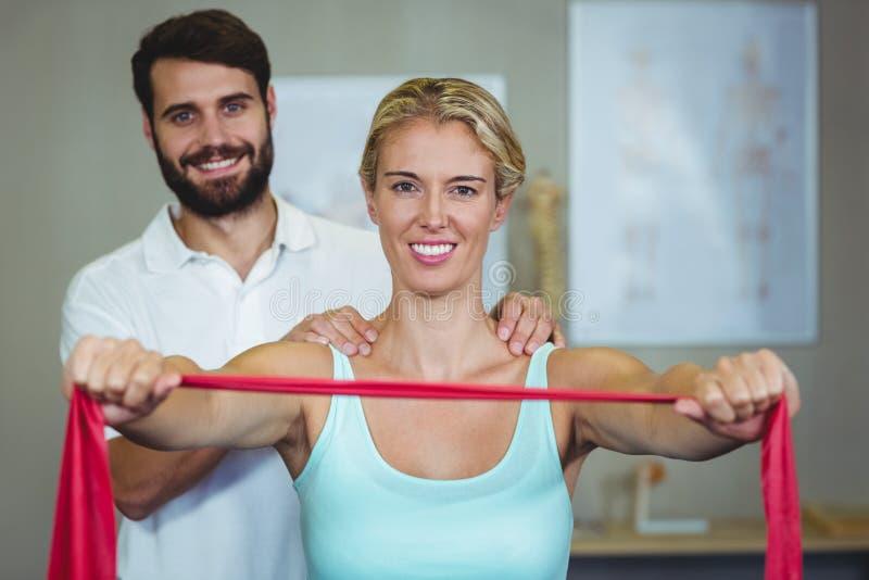 Manlig fysioterapeut som ger skuldramassage till den kvinnliga patienten royaltyfria foton