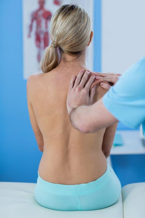 Manlig fysioterapeut som ger skuldramassage till den kvinnliga patienten royaltyfri bild