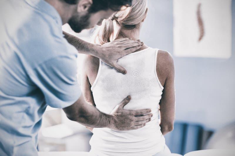 Manlig fysioterapeut som tillbaka ger massage till den kvinnliga patienten royaltyfri fotografi