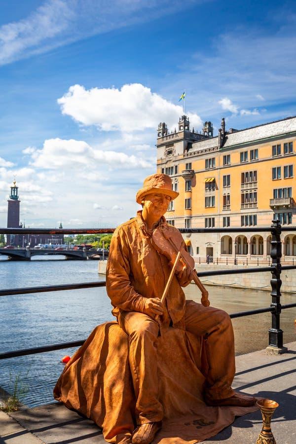 Manlig gataaktör på en bärande makeup för bro och guld- kulöra kläder royaltyfri foto