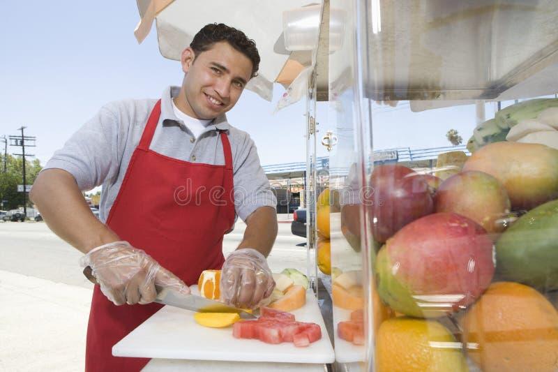 Manlig gatuförsäljare Chopping Fruits arkivfoton
