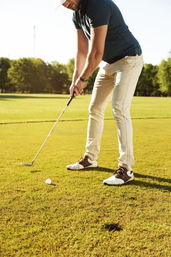 Manlig golfare omkring till utslagsplatsen av en golfboll royaltyfri fotografi