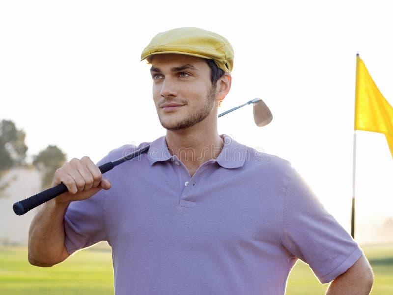 Manlig golfareinnehavklubba på golfbana royaltyfri foto