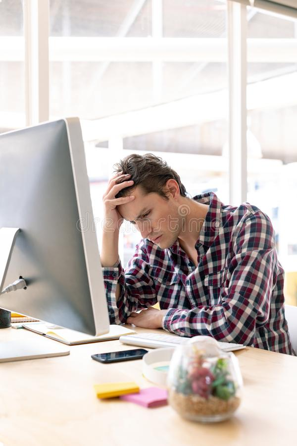 Manlig grafisk formgivare med handen på huvudet som sitter på skrivbordet i ett modernt kontor arkivfoto