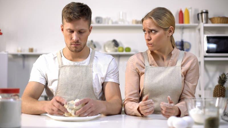 Manlig hållande rå deg, fru som obehagligt ser på maken, dålig kock, problem royaltyfri bild