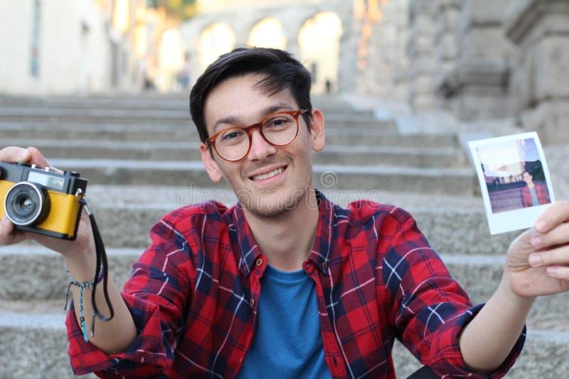 Manlig hållande retro kamera för gullig hipster och ögonblicklig filmbild royaltyfri foto