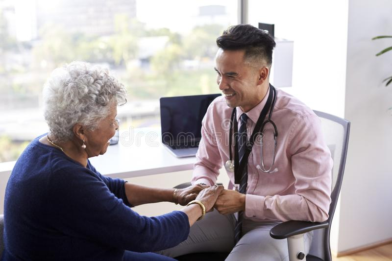 Manlig hög kvinnlig patient för doktor In Office Reassuring och rymma hennes händer royaltyfria foton