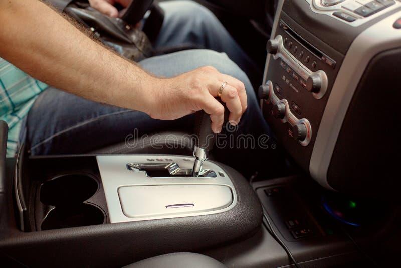 Manlig hand genom att anv?nda ett automatiskt kugghjul f?r bil K?rning av bilen med automatiskt kugghjulbegrepp arkivfoton