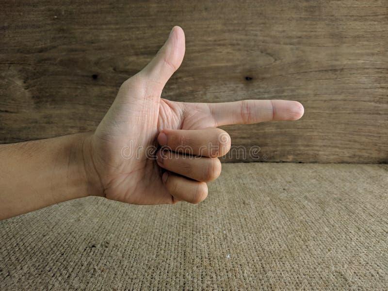 Manlig hand, i demonstrering av en gest av vapnet arkivfoto
