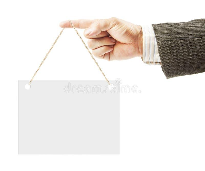 Manlig hand i punkter för en dräkt med hans finger åt sidan och en tom minnestavla med kopieringsutrymme som hänger på detta fing royaltyfria bilder