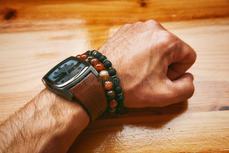 Manlig hand med klockan och armbanden royaltyfri bild