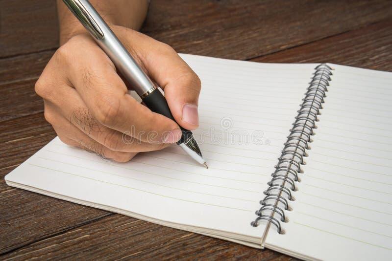 Manlig hand med pennhandstil på anteckningsboken royaltyfria bilder