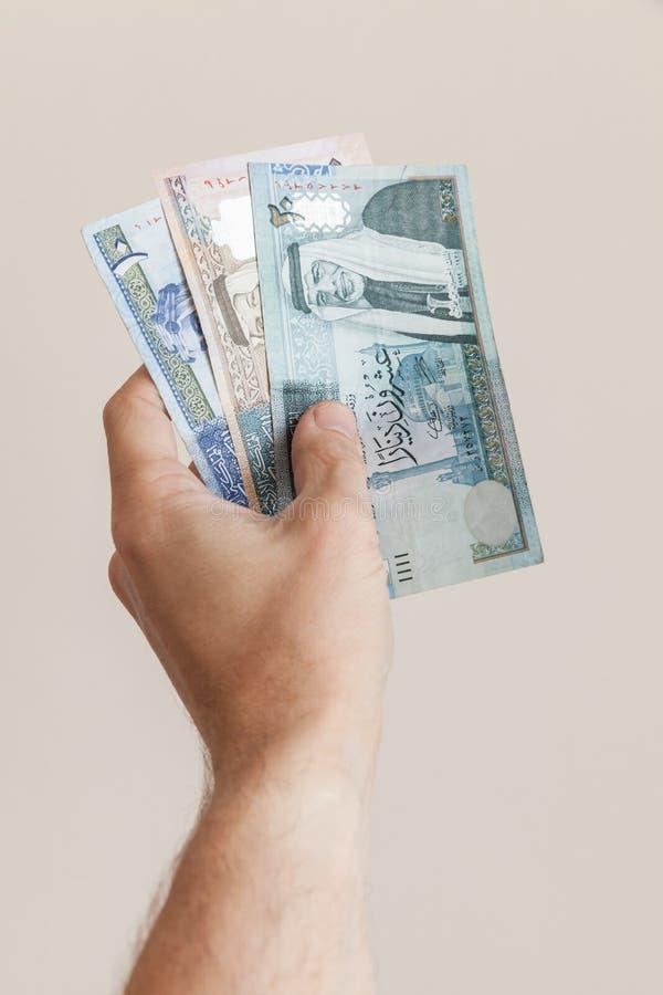 Manlig hand med sedlar för jordanska dinar royaltyfria foton