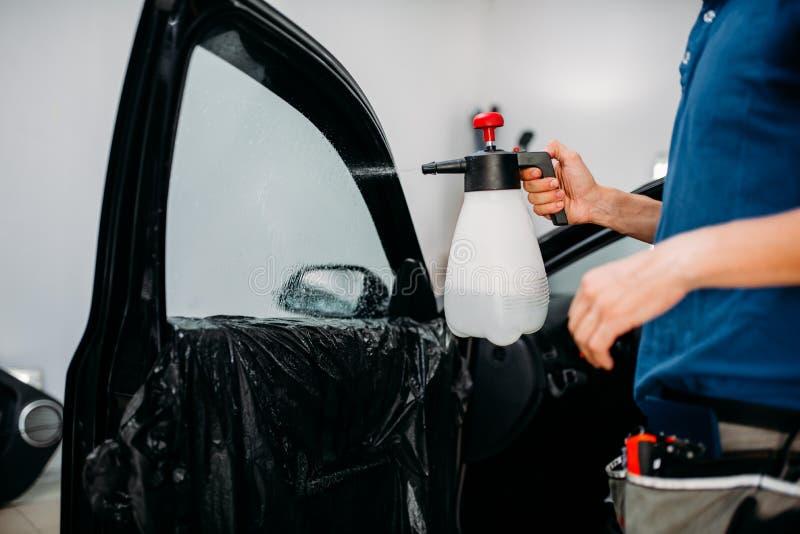Manlig hand med sprej, installation för ton för bilfönster royaltyfri fotografi