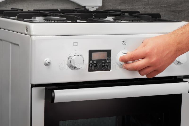 Manlig hand som är roterande på den vita kökgasugnen på grå färger fotografering för bildbyråer