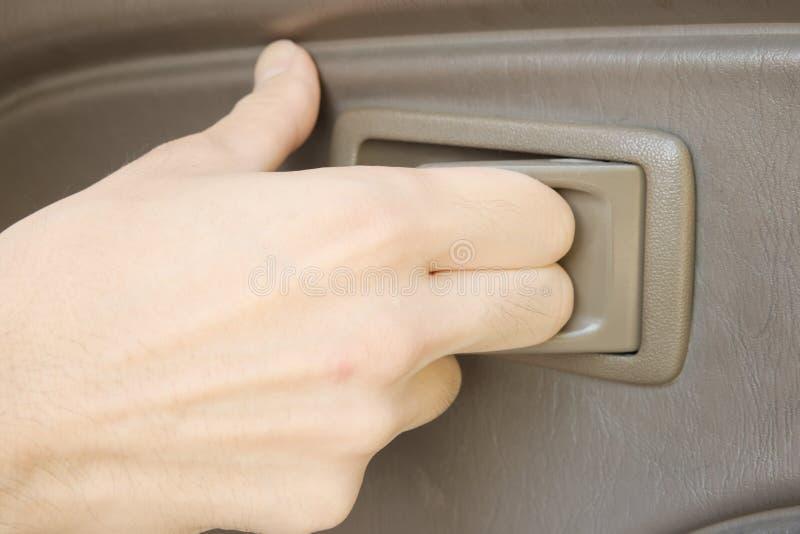 Manlig hand som drar det plast- handtaget till den öppna bildörren royaltyfria bilder