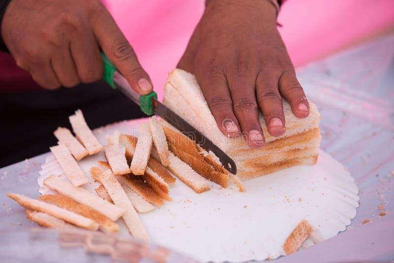 Manlig hand som klipper nytt bröd på tabellbrödnärbild Nytt br?d p? k?ksbordet royaltyfria bilder