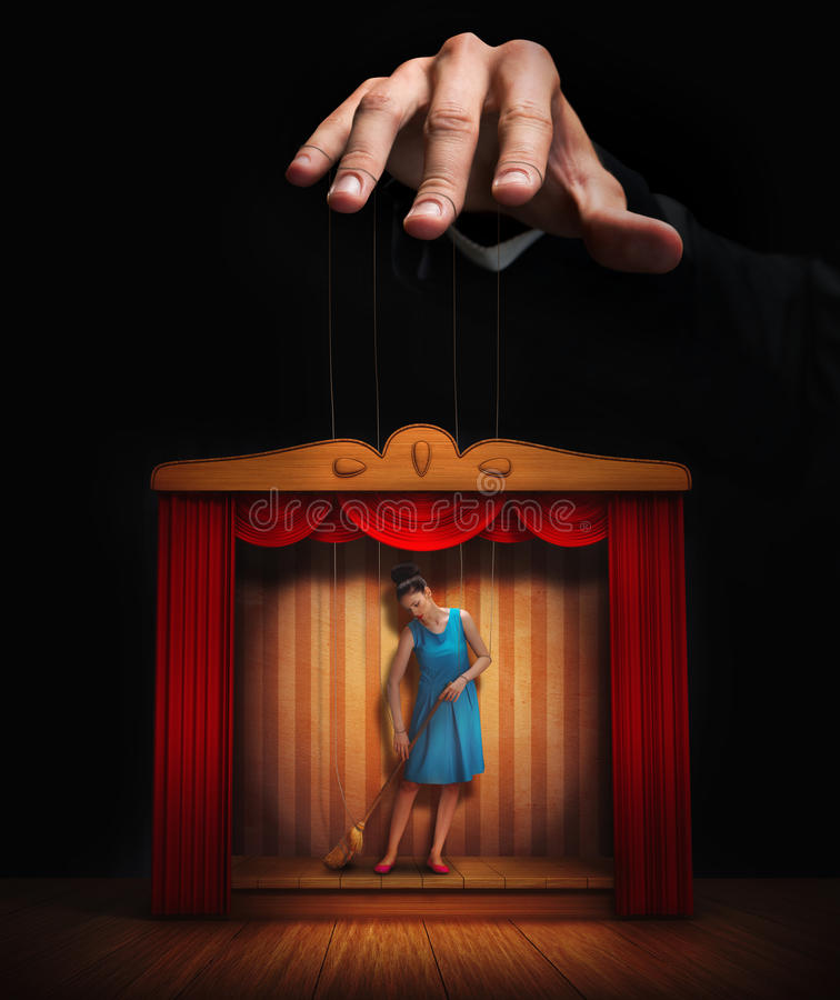 Manlig hand som kontrollerar en liten kvinnadocka arkivbild