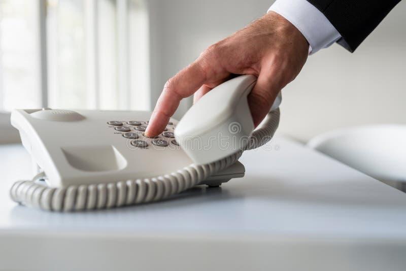 Manlig hand som ringer ett telefonnummer för att göra en telefon ca royaltyfri fotografi