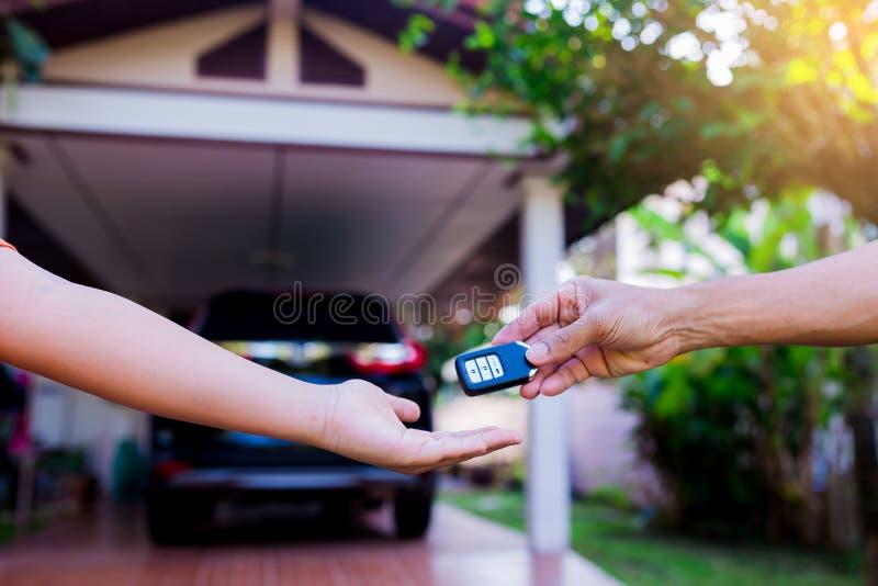 Manlig hand som rymmer en avlägsen biltangent och över räcker den för att ge a royaltyfri bild