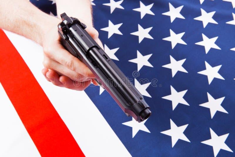 Manlig hand som rymmer en handeldvapen ovanför satängUSA-flaggan med två händer - studiofors arkivfoton