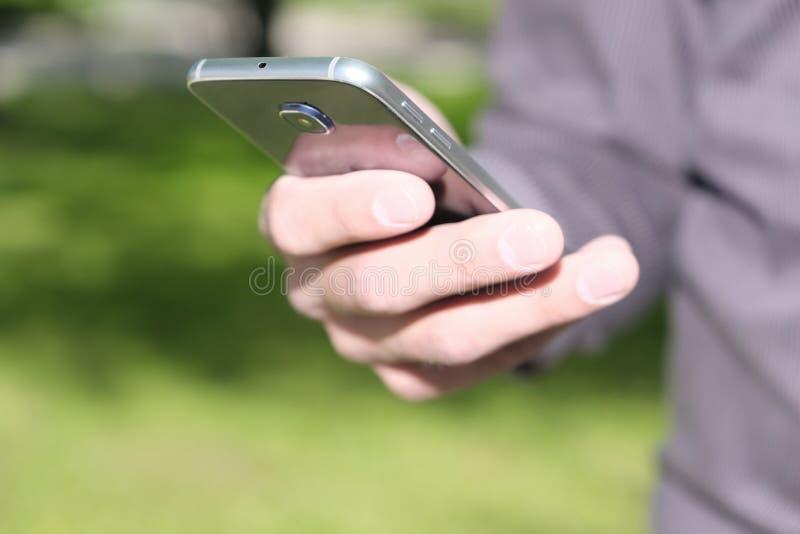 Manlig hand som rymmer en mobiltelefon fotografering för bildbyråer