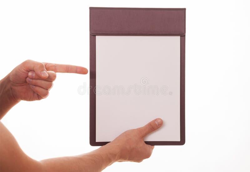 Manlig hand som rymmer en skrivplatta med det tomma arket av papper och indien arkivbild