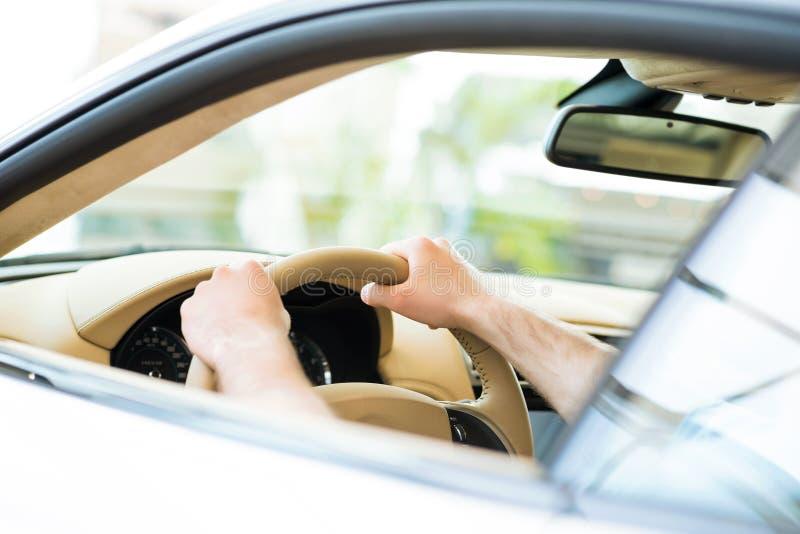Manlig hand som rymmer ett bilhjul royaltyfria foton