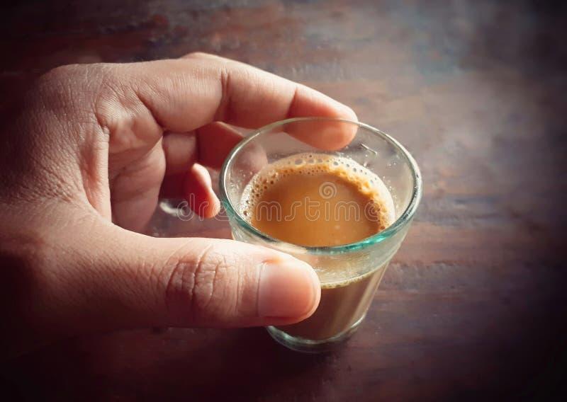 Manlig hand som rymmer ett litet exponeringsglas av te royaltyfri foto