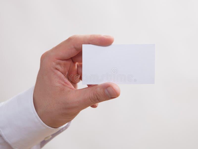 Manlig hand som rymmer ett tomt affärskort royaltyfria foton