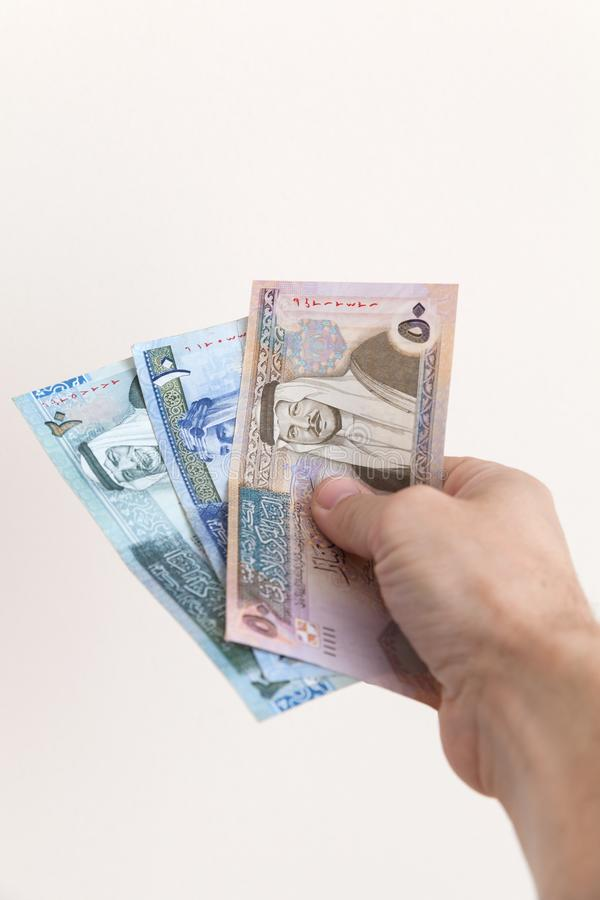 Manlig hand som rymmer jordanska dinar royaltyfri bild