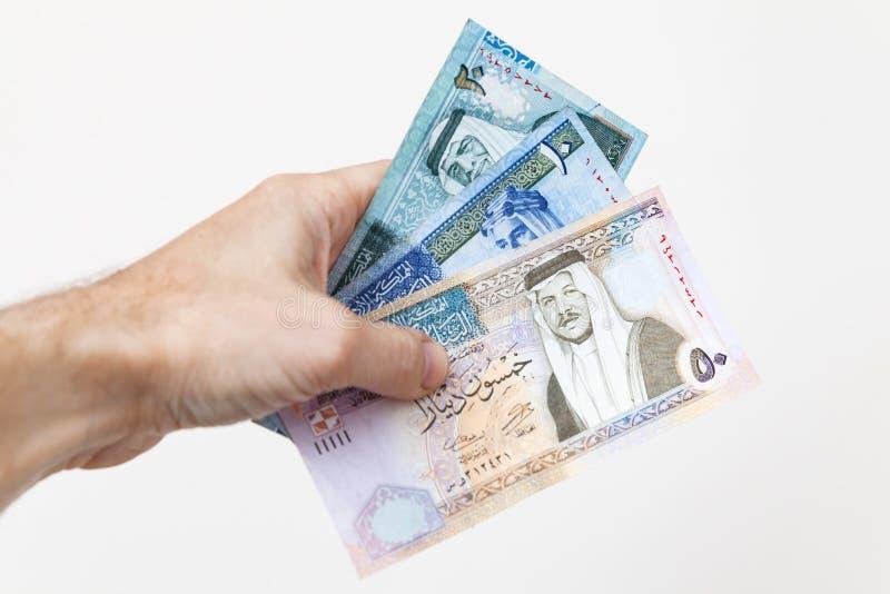 Manlig hand som rymmer jordanska dinar royaltyfri foto