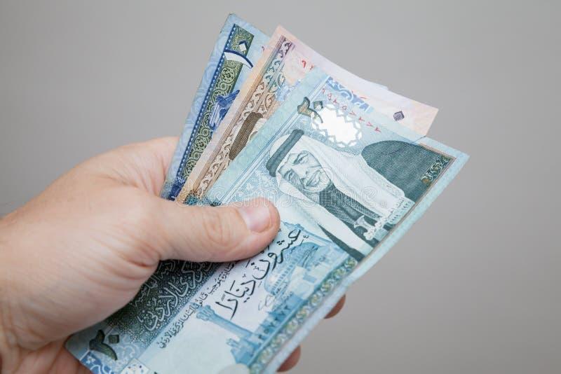 Manlig hand som rymmer jordanska dinar royaltyfria foton