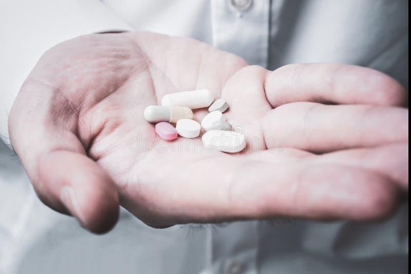 Manlig hand som rymmer några preventivpillerar - ta läkarbehandlingbegrepp arkivbilder