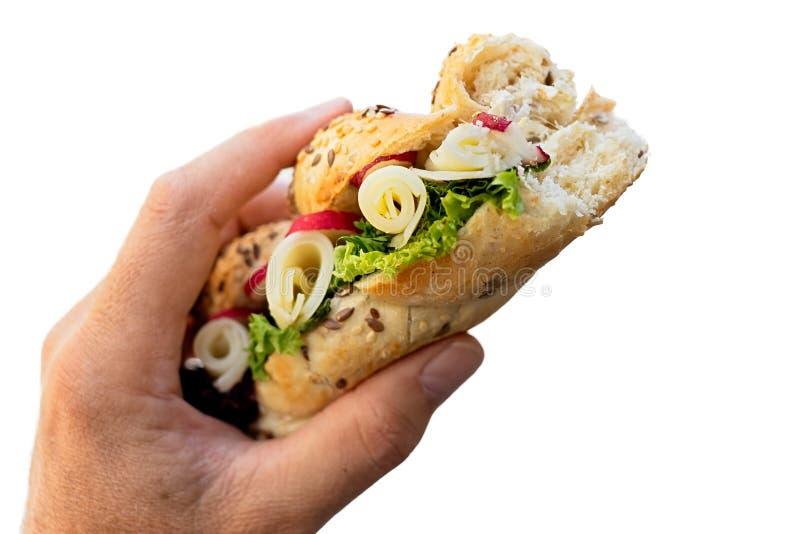 Manlig hand som rymmer partlially ätit frasigt helt för ost och för sallad arkivfoto