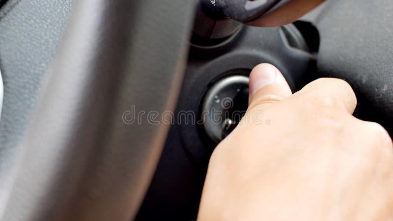 Manlig hand som sätter in biltangent in i låset och startar motorn royaltyfria foton
