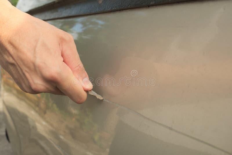 Manlig hand som skrapar en bil arkivfoto