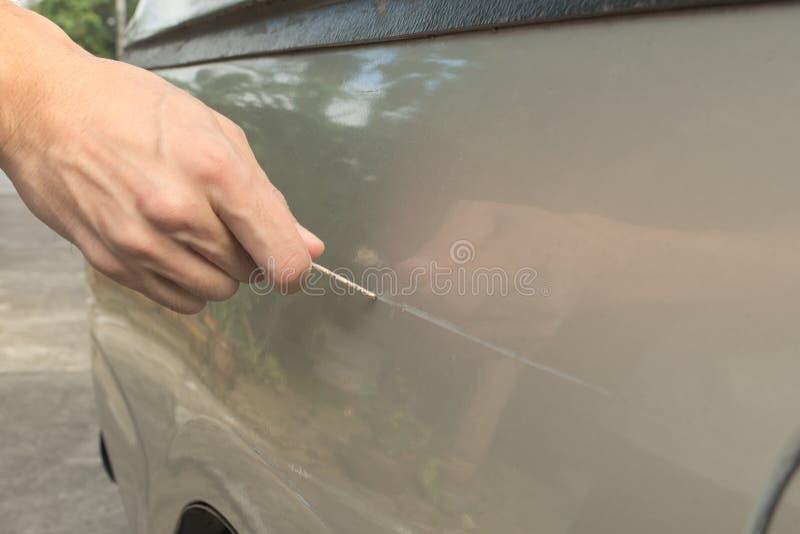 Manlig hand som skrapar en bil royaltyfri foto