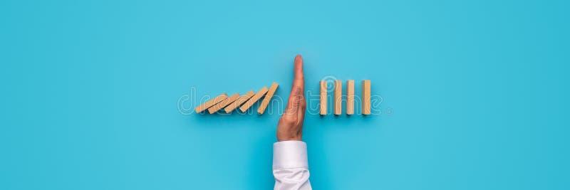 Manlig hand som stoppar fallande dominobrickor royaltyfria bilder