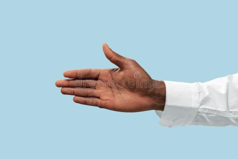 Manlig hand som visar en gest av att invitera som isoleras på blå bakgrund arkivbild