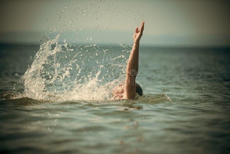 Manlig hand ut ur havet med färgstänk av vatten Simningbegrepp Grabbsimning under havsvatten, horisont på bakgrund, baksida royaltyfri bild
