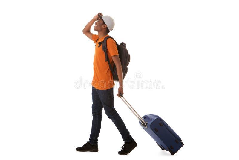 Manlig handelsresande för full afrikansk amerikan för längd som lycklig går med resväskan mot isolerad vit bakgrund royaltyfri fotografi
