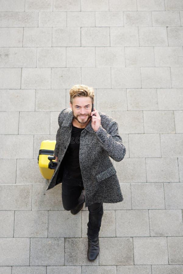 Manlig handelsresande som går med mobiltelefonen och påsen arkivfoto