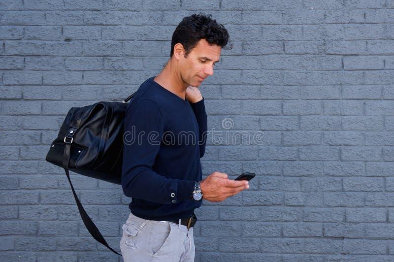 Manlig handelsresande som går med mobiltelefonen och påsen royaltyfria bilder