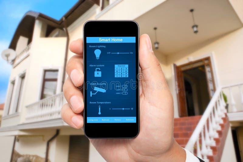 Manlig handhåll en telefon med det smarta huset för system på bakgrunden royaltyfri bild