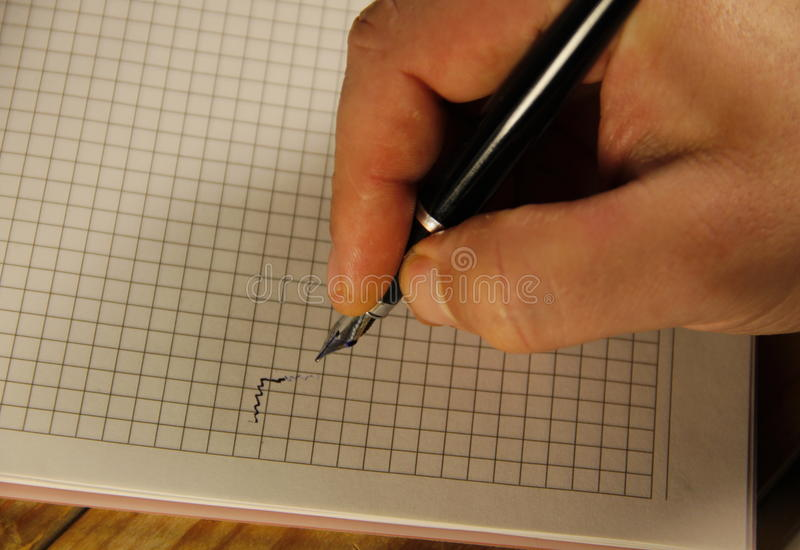 Manlig handhandstil genom att använda reservoarpennan på en anteckningsbok royaltyfria foton