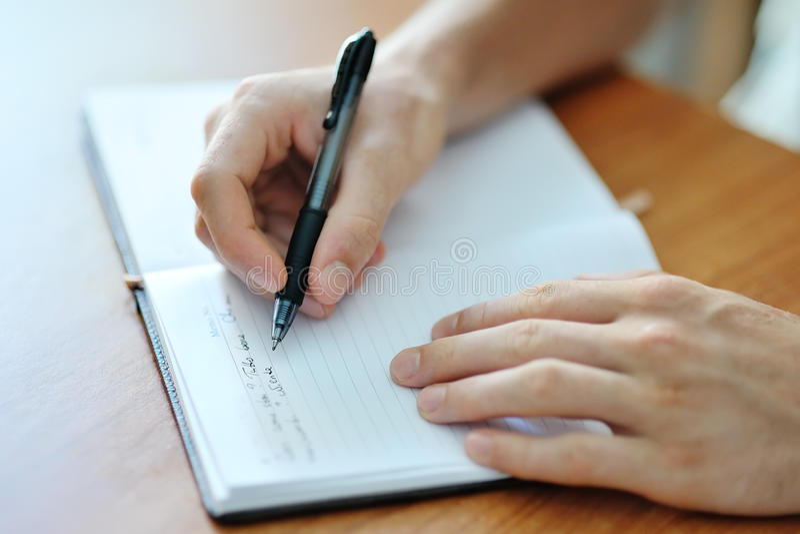 Manlig handhandstil på en anteckningsbok fotografering för bildbyråer