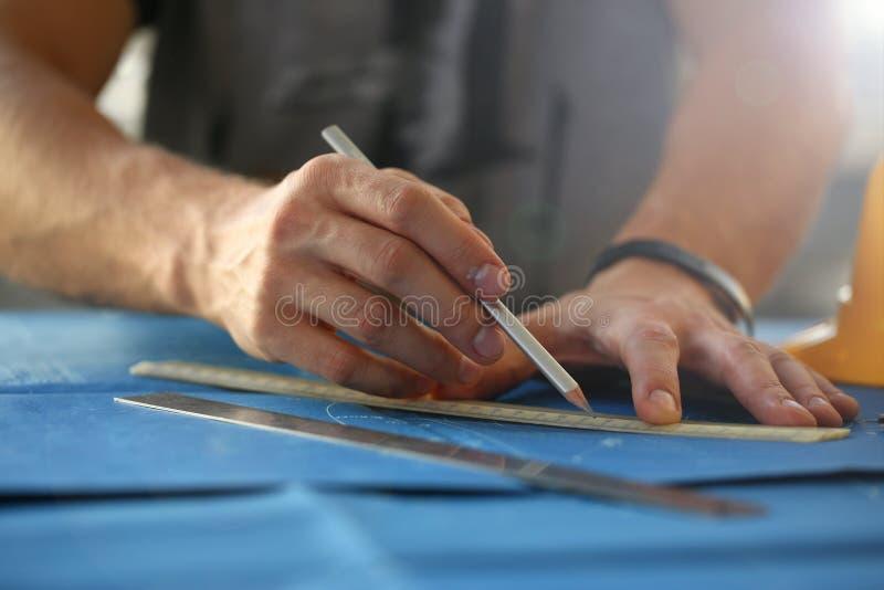 Manlig handinnehavblyertspenna i hand arkivbild